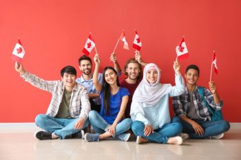 Group,Of,Students,With,Canadian,Flags,Sitting,Near,Color,Wall
